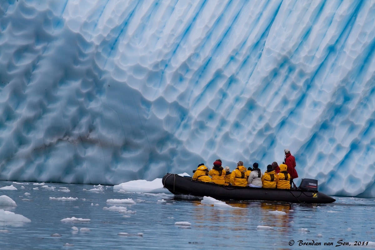 A group of zodiac cruisers admire the Antarctic Iceberg as close as possible.  The scale of the huge ice in comparison to the boat gives some perspective to the size of these icebergs.