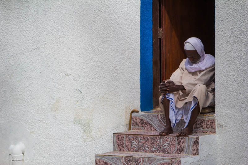An Omani man sleeping on his steps in the heat of the day.