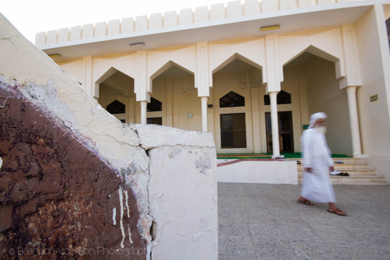A man walks past a mosque in Oman