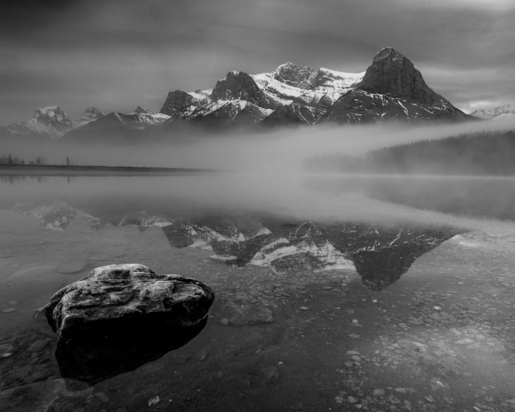 A black and white image of a rock in a lake in front of a mountain reflection.
