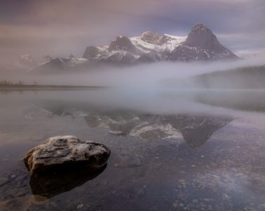 A rock sits in the lake in front of mountain in Canmore, Canada.