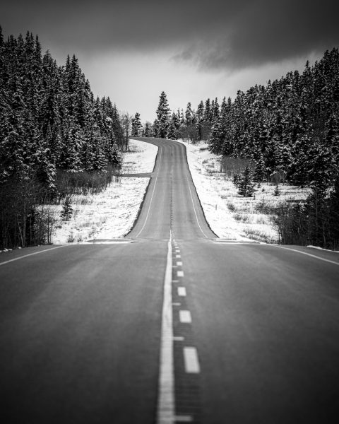Black and white photo of a road through the snow in Canada